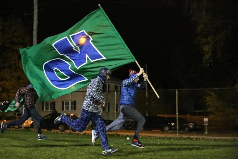 Students run into the game with the Notre Dame flag.