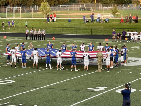 Players from Notre Dame, Green Bay West join the Army National Guard at midfield to present the American flag prior to Fridays kickoff